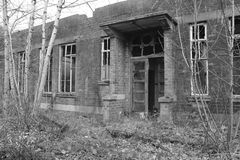 Old, creepy, abandoned building. Falling apart with shattered windows. Black and white Royalty Free Stock Photos