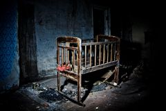 Old creepy eerie wooden baby crib in abandoned house. Horror concept.  stock photos