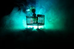 Old creepy eerie wooden baby crib in dark toned foggy background. Horror concept. Scary baby and bed silhouette in dark royalty free stock images