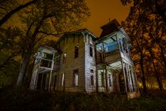Old creepy wooden abandoned haunted mansion at night Stock Image