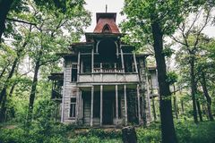Old creepy wooden abandoned haunted mansion. House building among green forest Stock Photography