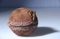 Old cricket ball. Details of old used cricket ball on light blue background Stock Photography