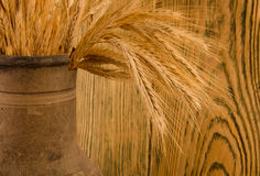 Old crock with a bunch of wheat ears Stock Photo