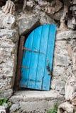 Old crooked blue wooden door in Crete Greece. Old crooked blue wooden door in Crete, Greece Royalty Free Stock Photo