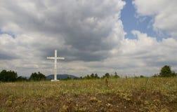 Old cross in the field. Old cross in the field against blue sky Royalty Free Stock Photography