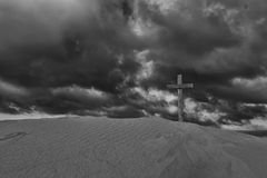 An old cross on sand dune next to the ocean with a calm sunrise Stock Photos