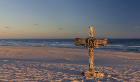 An old cross on sand dune next to the ocean with a calm sunrise. An old cross on a sand dune next to the ocean with a calm sunrise Royalty Free Stock Image