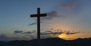 An old cross on sand dune next to the ocean with a calm sunrise Stock Image