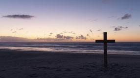 An old cross on sand dune next to the ocean with a calm sunrise Royalty Free Stock Photos