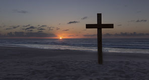 An old cross on sand dune next to the ocean with a calm sunrise Stock Photo