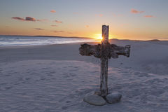 An old cross on sand dune next to the ocean with a calm sunrise Royalty Free Stock Images