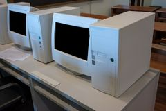 Old CRT computer monitors and towers. In classroom stock photo