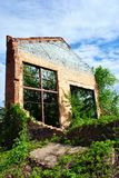 Old crumbling brick wall with window without glass, green trees and blue cloudy sky. Old crumbling brick wall with window without glass, green trees and blue stock photography
