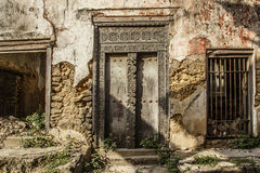 Old crumbling building with Zanzibarian wooden door Stock Images
