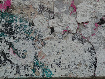Old,  crumbling wall with multi-colored paint splashes Stock Images