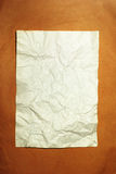 Old crumpled paper on brown background Stock Image