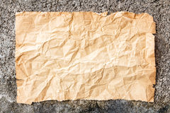 Old crumpled paper on cement wall Royalty Free Stock Photography