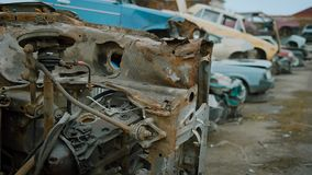 Old crushed cars is lying in heaps on a rubbish dump outdoors in cloudy autumn day, view on rusty corroded bodies of