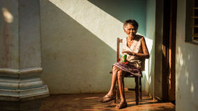 Old Cuban woman on chair enjoying a beer Stock Photography