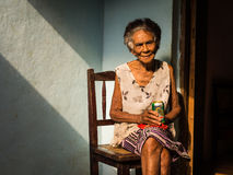 Old Cuban woman on chair enjoying a beer Royalty Free Stock Photo