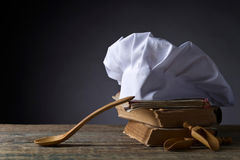 Old culinary books , chef hat and wooden spoons . Royalty Free Stock Image