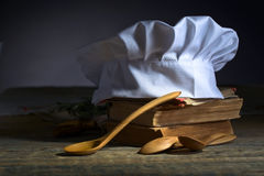 Old culinary books , chef hat and wooden spoons . Stock Photo