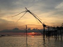 Old culture traditional fishing at lake by wooden square dip net in the sunrise of morning time. Good morning the sun!. Beautiful silhouette background stock images