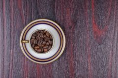 An old cup full of coffee beans with its plate stock photo