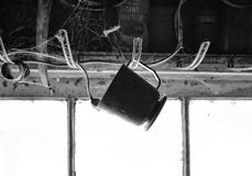 Old cup hanging from a hook in black and white Royalty Free Stock Photo