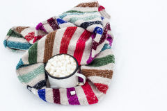 Old cup of hot cocoa with marshmallows and a soft colorful knitt Stock Image