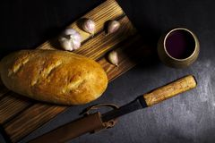 Cup of wine with bread, vegetables on dark background stock photo