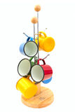 Old cups. A group of brightly coloured tin cups hung from a wooden cup holder Royalty Free Stock Photography