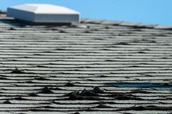 Old roof shingles. Old and curled asphalt roof shingles and an air vent stock images