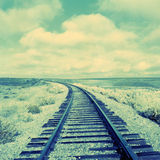 Old curved railway tracks. A set of left curving railway tracks going into the distance. Horizon in the middle of image and sky above. Picture is slightly royalty free stock photo