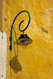 Old curved street lamp. Street lamp with shadow on the wall Royalty Free Stock Photo