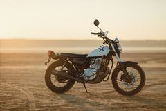 Old custom beautiful cafe racer motorcycle in the desert at sunset or sunrise. Old custom beautiful cafe racer motorcycle in the desert at sunset royalty free stock photography