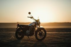 Old custom beautiful cafe racer motorcycle in the desert at sunset or sunrise. Old custom beautiful cafe racer motorcycle in the desert at sunset royalty free stock images