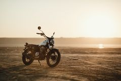 Old custom beautiful cafe racer motorcycle in the desert at sunset or sunrise. Old custom beautiful cafe racer motorcycle in the desert at sunset royalty free stock photos
