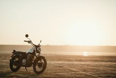 Old custom beautiful cafe racer motorcycle in the desert at sunset or sunrise. Old custom beautiful cafe racer motorcycle in the desert at sunset stock photo