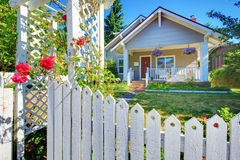 OLd cute grey house exterior behind white fence. royalty free stock image