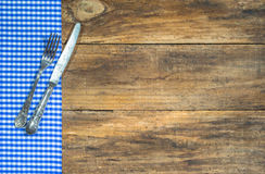 Old cutlery with blue and white table cloth on rustic wood. Stock Photography