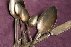 Old cutlery in silver. Closeup of old cutlery in silver on purple background Stock Image