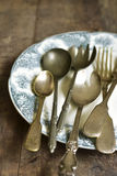 Old cutlery on a vintage plate. Royalty Free Stock Images