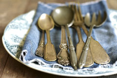 Old cutlery on a vintage plate. Royalty Free Stock Photography