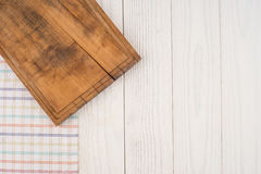 An old cutting board in the kitchen napkin on white wooden table Royalty Free Stock Photos