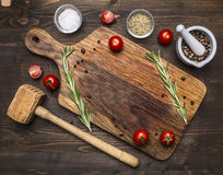 Old cutting board with spices and herbs for cooking meat with cherry tomatoes and a hammer meat place for text,frame. Old cutting board with spices and herbs for Stock Image