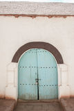 Old cyan gate. On a white wall Royalty Free Stock Photography