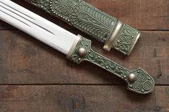Old Dagger. Closeup of antique caucasian dagger and scabbard on wooden background royalty free stock image