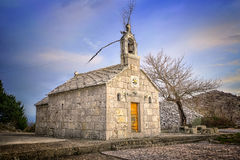 Old Dalmatian stone church with blue sky. HDR image of an old, rusty, Dalmatian church with naked tree and blue sky in the background Stock Photos