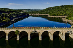 Old dam. The old dam that controls the river in the center of Sardinia. the green hills are reflected in the water Stock Photography